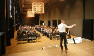 Martin Koenig standing on stage in front of audience - auf die buehne